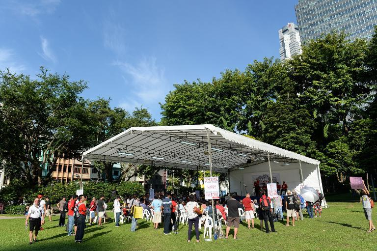 People listen to speakers during a rally at speakers corner in Singapore on October 5, 2013