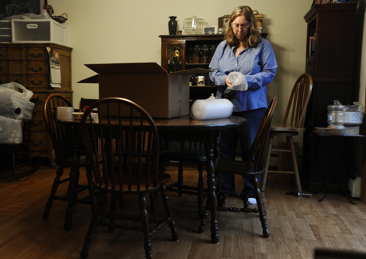 In this Dec. 23, 2013 photo, Leslie Lynch packs up belongings in her dining room in Glastonbury, Conn. Lynch who lost her job last year is moving out of her home of 21 years because she can no longer afford the mortgage payments. (AP Photo/Jessica Hill)