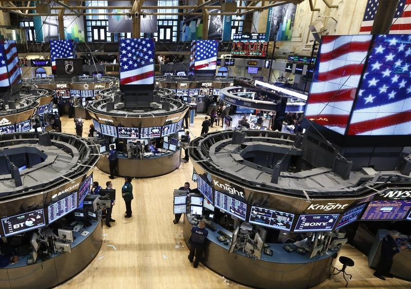 Traders work on the floor at the New York Stock Exchange just following the closing bell