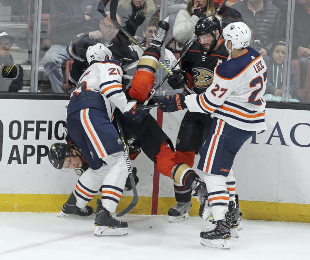 Anaheim Ducks defenseman Brandon Montour, left, is upended as he tangles with Edmonton Oilers defenseman Darnell Nurse (25) and left winger Milan Lucic in the second period of an NHL hockey game in Anaheim, Calif., Sunday, Feb. 25, 2018. (AP Photo/Reed Saxon)