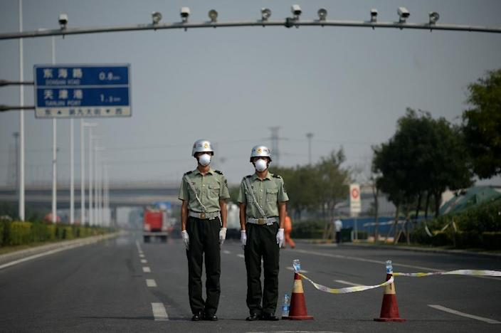 Two soldiers wearing face masks stand at a checkpoint in Tianjin near the site of the explosions at a chemical warehouse that hit the city a few days before on August 16, 2015 (AFP Photo/Wang Zhao)