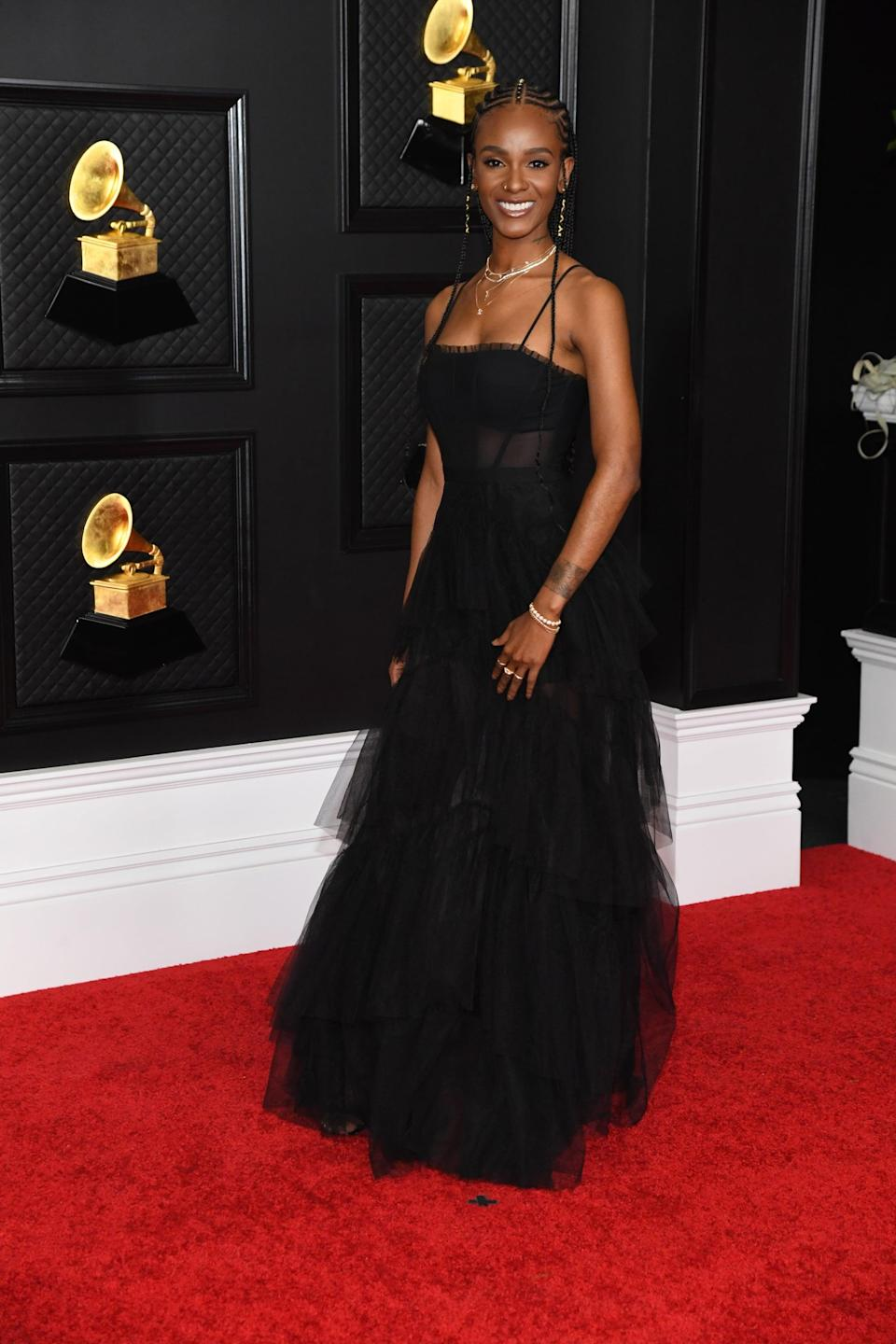 <p>Wearing a black tulle tiered dress.</p>