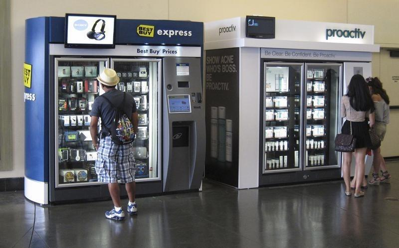Customers examine products for sale in vending machines at a shopping mall in Hollywood, California