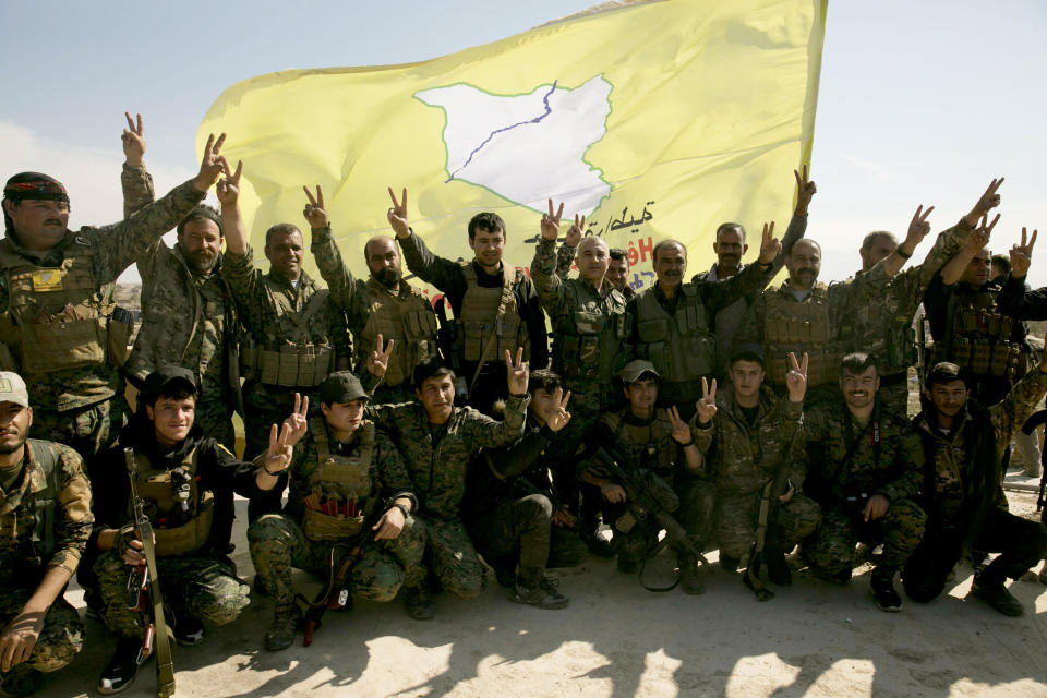 U.S.-backed Syrian Democratic Forces (SDF) fighters pose for a photo on a rooftop overlooking Baghouz, Syria, after the SDF declared the area free of Islamic State militants after months of fighting last March. (Photo: Maya Alleruzzo/AP)
