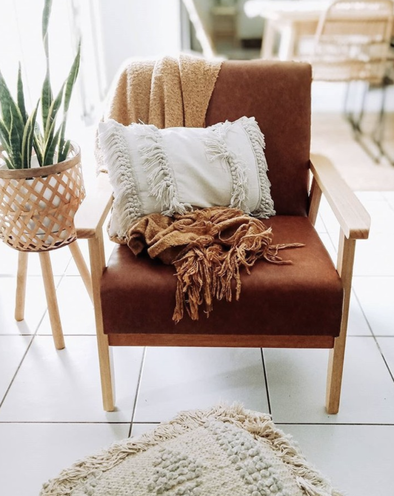 A copper armchair with a white fringed cushion