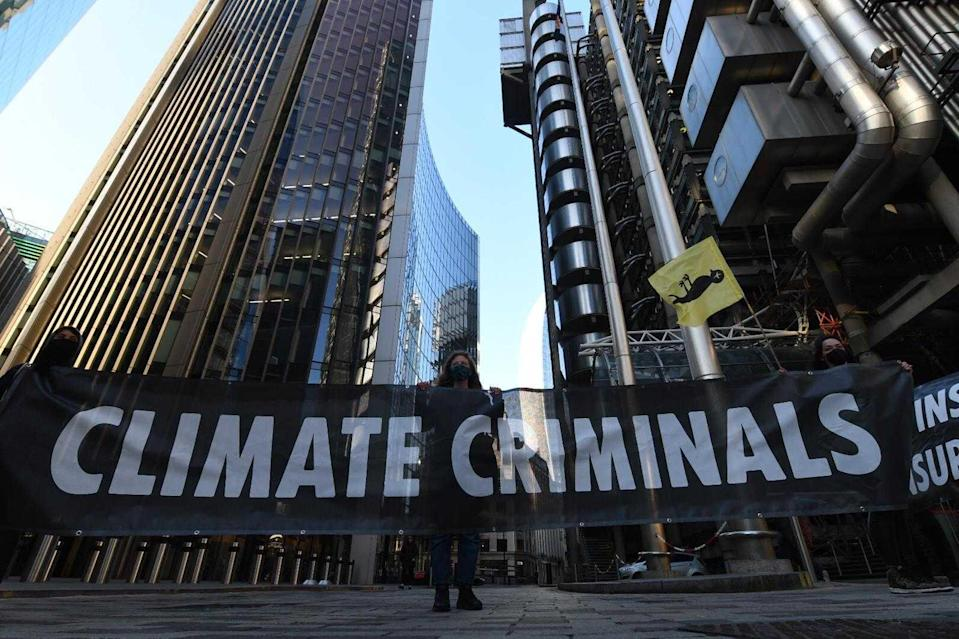 An activist stands next to a 'climate criminals' banner outside Lloyd'sGareth Morris