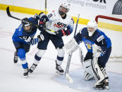 Finland's Tanja Niskanen, left, checks Grace Zumwinkle, center, of the United States, as Finland goalie Anni Keisala looks on during the first period of an IIHF women's hockey championships semifinal in Calgary, Alberta, Monday, Aug. 30, 2021. (Jeff McIntosh/The Canadian Press via AP)