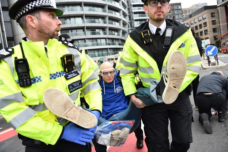An Insulate Britain protester carried away by police from Old Street roundabout on Friday (AFP via Getty Images)