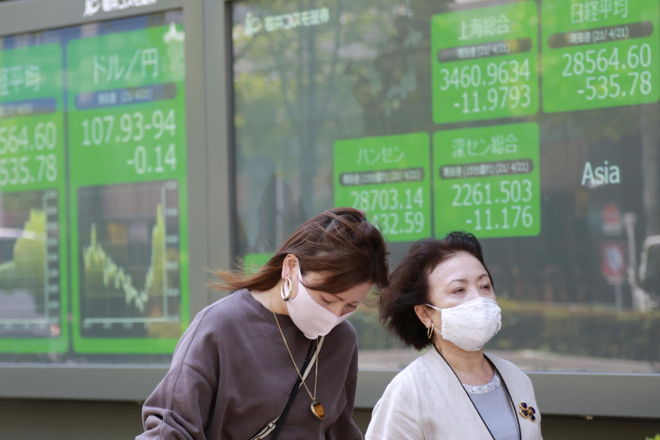 People walk by an electronic stock board of a securities firm in Tokyo, Wednesday, April 21, 2021. Shares skidded in Asia on Wednesday after Wall Street closed lower for a second straight day, led by drops in technology companies and banks. (AP Photo/Koji Sasahara)