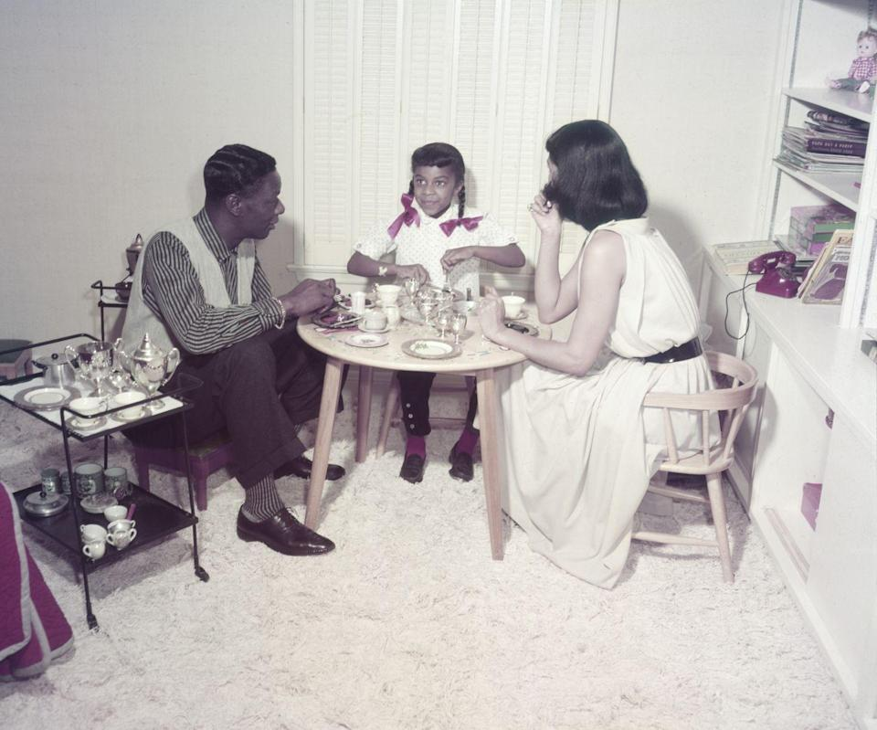 <p>Nat King Cole and Maria Cole raised their five children in the brick English Tudor-style house, which they bought in 1948. Here, they have tea with their daughter Natalie in her playroom. </p>