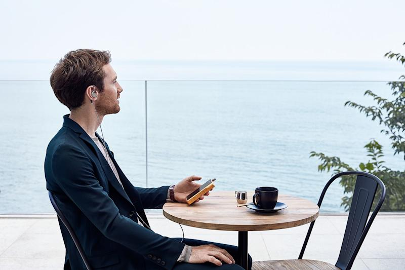 A man sitting at a small circular table with earbuds in holding a phone. The table is overlooking a large body of water.
