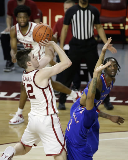 Oklahoma guard Austin Reaves (12) takes a shot against Kansas guard Dajuan Harris (3) while Oklahoma guard Elijah Harkless (24) and Kansas guard Marcus Garrett (0) look on during the second half of an NCAA college basketball game in Norman, Okla., Saturday, Jan. 23, 2021. (AP Photo/Garett Fisbeck)