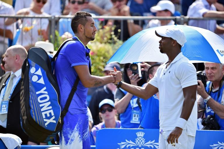 Australia's Nick Kyrgios (L) shakes hands with US player Donald Young after having to retire during their men's singles first round match at Queen's Club in west London on June 19, 2017
