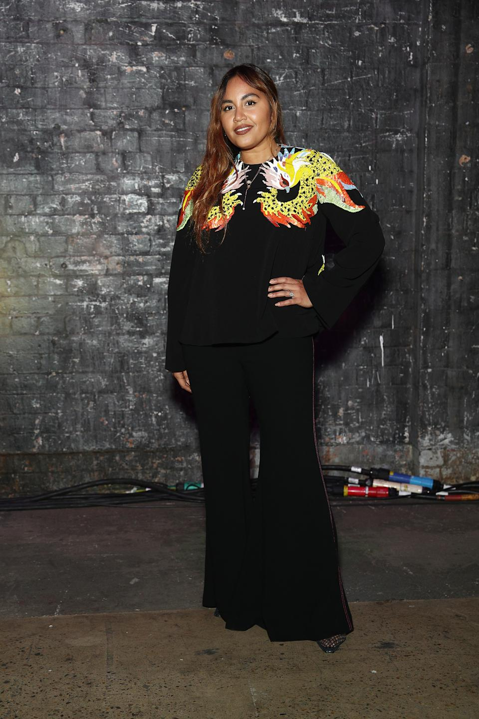 Jessica Mauboy wears a black pants and top with yellow and orange sequin detailing at the Romance Was Born show during Afterpay Australian Fashion Week 2021 Resort '22 Collections at Carriageworks on May 31, 2021 in Sydney, Australia