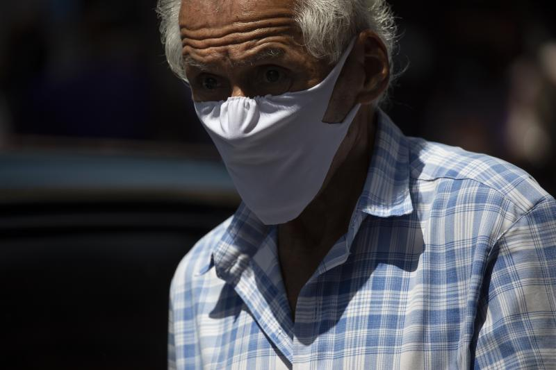 A man wears a homemade face mask as a preventive measure against the spread of the new coronavirus in Caracas, Venezuela, Thursday, March 26, 2020. COVID-19 causes mild or moderate symptoms for most people, but for some, especially older adults and people with existing health problems, it can cause more severe illness or death. (AP Photo/Ariana Cubillos)