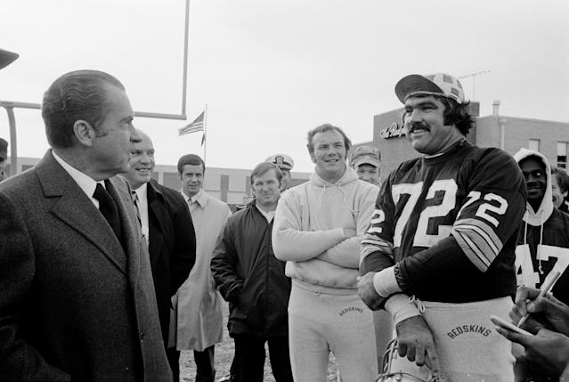 President Richard Nixon visits with the Washington Redskins in 1971, talking with defensive tackle Diron Talbert as quarterback Sam Wyche looks on. (Nate Fine/Getty Images)