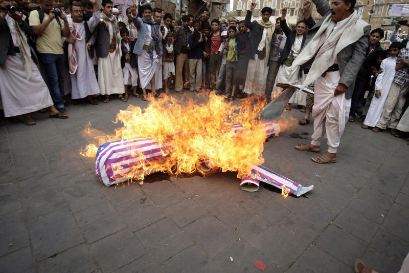 FILE - In this Friday, April 12, 2013 file photo, members of the Yemeni al-Houthi Shiite rebel group burn an effigy of a U.S. aircraft during a demonstration to protest against the U.S. and Saudi interference in Yemen, after Friday prayer in Sanaa, Yemen. A public backlash is starting to grow in Yemen over civilians killed by American drones as the U.S. dramatically steps up its strikes against al-Qaida's branch here the past year. Relatives of those killed say the missile blasts hitting their towns only turn Yemenis against the U.S. campaign to crush militants. (AP Photo/Hani Mohammed)