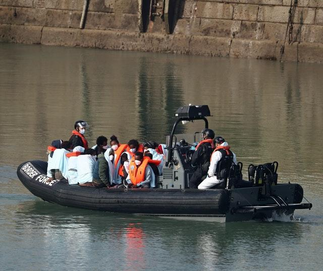 A group of people, thought to be migrants, are ferried ashore by Border Force officers at Dover marina in Kent