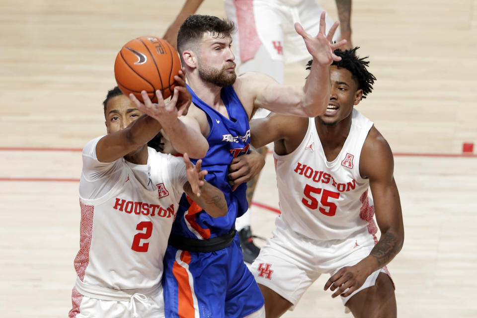 Houston guard Caleb Mills (2) strips a pass away from Boise State forward Mladen Armus, center, as forward Brison Gresham (55) looks on during the first half of an NCAA college basketball game Friday, Nov. 27, 2020, in Houston. (AP Photo/Michael Wyke)