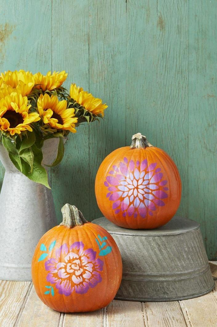 """<p>Recreate this fun look by getting some <a href=""""https://go.redirectingat.com?id=74968X1596630&url=https%3A%2F%2Fwww.etsy.com%2Fmarket%2Flarge_flower_stencil&sref=https%3A%2F%2Fwww.womansday.com%2Fhome%2Fdecorating%2Fg1902%2Fpainted-pumpkins-ideas%2F"""" rel=""""nofollow noopener"""" target=""""_blank"""" data-ylk=""""slk:big flower stencils"""" class=""""link rapid-noclick-resp"""">big flower stencils</a> and craft paint, then going to town. Use a foam pouncer to gently dab your lightest color of paint at the center, then gradually use darker paint colors towards the outer edge. </p><p><strong><em>Get the tutorial from <a href=""""https://www.thepioneerwoman.com/holidays-celebrations/g32223401/pumpkin-decorating-ideas"""" rel=""""nofollow noopener"""" target=""""_blank"""" data-ylk=""""slk:The Pioneer Woman."""" class=""""link rapid-noclick-resp"""">The Pioneer Woman.</a></em></strong></p>"""