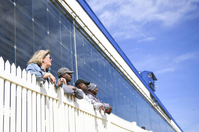 Workers watch from the railing at Laurel Park Race Track as horse races are held without spectators, Saturday, March 14, 2020, in Laurel, Md. While most of the sports world is idled by the coronavirus pandemic, horse racing runs on. (AP Photo/Terrance Williams)