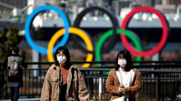 FILE PHOTO: People wearing protective face masks, following an outbreak of the novel coronavirus, are seen in front of the Giant Olympic rings at the waterfront area at Odaiba Marine Park in Tokyo, Japan, Feb. 27, 2020. (Athit Perawongmetha/Reuters)