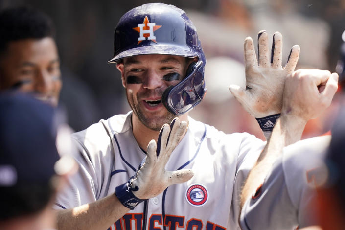 Houston Astros' Chas McCormick is congratulated by teammates after hitting a two-run home run in the sixth inning of a baseball game against the Cleveland Indians, Sunday, July 4, 2021, in Cleveland. (AP Photo/Tony Dejak)