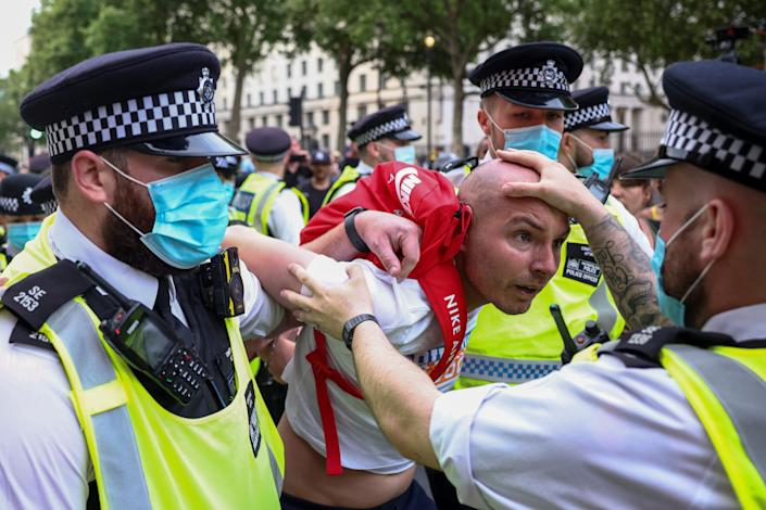 Three London police officers detain a anti-lockdown protestor on a sunny afternoon