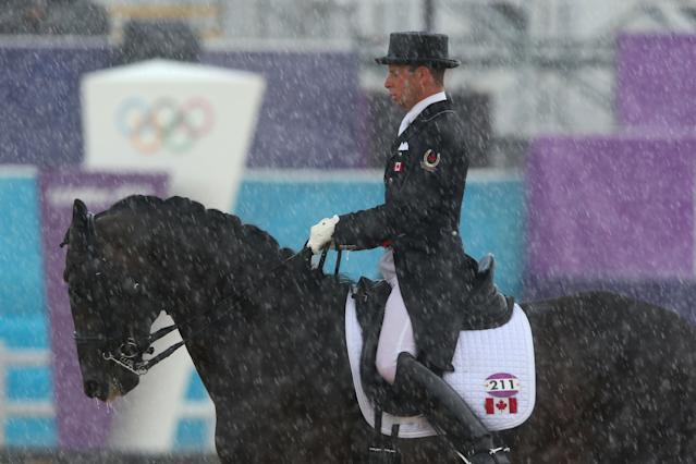 LONDON, ENGLAND - AUGUST 02: David Marcus of Canada riding Capital during a rain shower in the Dressage Grand Prix on Day 6 of the London 2012 Olympic Games at Greenwich Park on August 2, 2012 in London, England. (Photo by Alex Livesey/Getty Images)
