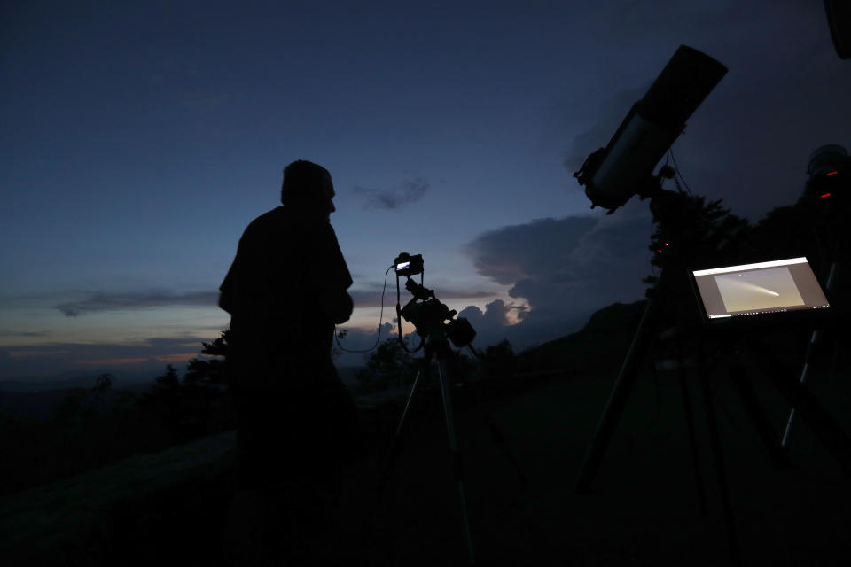 As the sun sets at Grandfather Mountain astrophotographer Johnny Horne makes exposures of the evening sky as he waits for Comet NEOWISE to appear from behind storm clouds Friday, July 17, 2020 in Linville, N.C. (AP Photo/Gerry Broome)