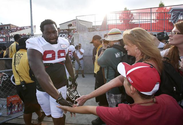 Atlanta Falcons defensive end Tyson Jackson (99) greets fans as he walks onto the field for Friday Night Lights, at Archer High School on Friday, Aug. 1, 2014, in Lawrenceville, Ga. The Falcons continued their tradition of staging NFL football practice at an area high school each year. (AP Photo/Jason Getz)