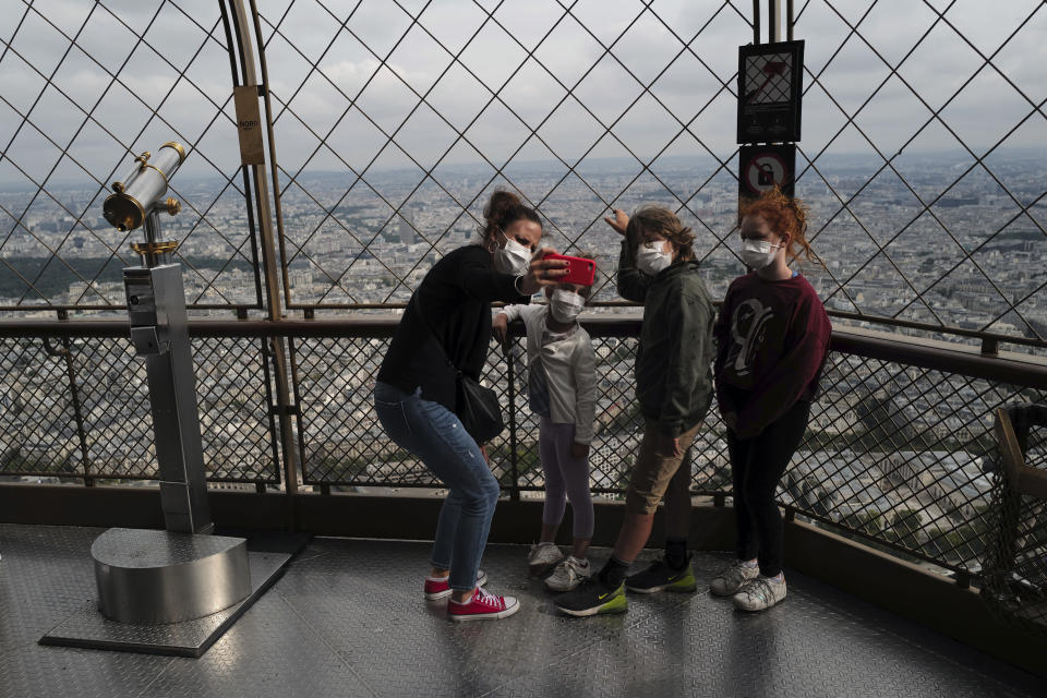 French visitors from south of France, Caroline, left, with her kids, Oxane, Rafaelle and Emma, from left to right, take a selfie from the third level during the opening up of the top floor of the Eiffel Tower, Wednesday, July 15, 2020 in Paris. The top floor of Paris' Eiffel Tower reopened today as the 19th century iron monument re-opened its first two floors on June 26 following its longest closure since World War II. (AP Photo/Francois Mori)