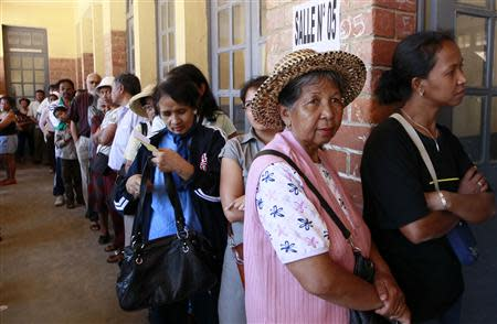 People line up before voting at a polling centre in the capital Antananarivo
