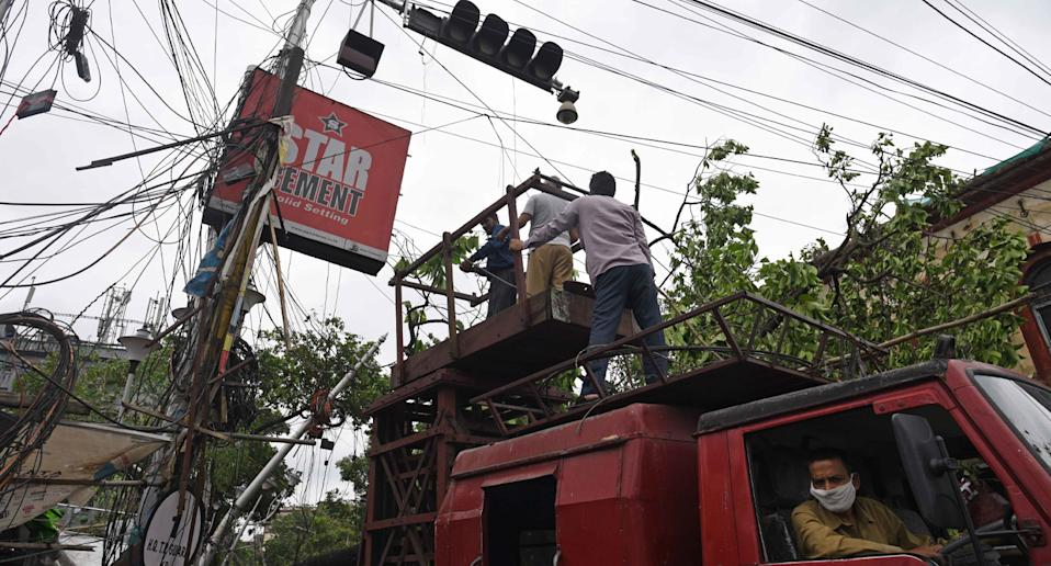 Technicians shown tending to destroyed power lines in Kolkata, India. Source: AAP