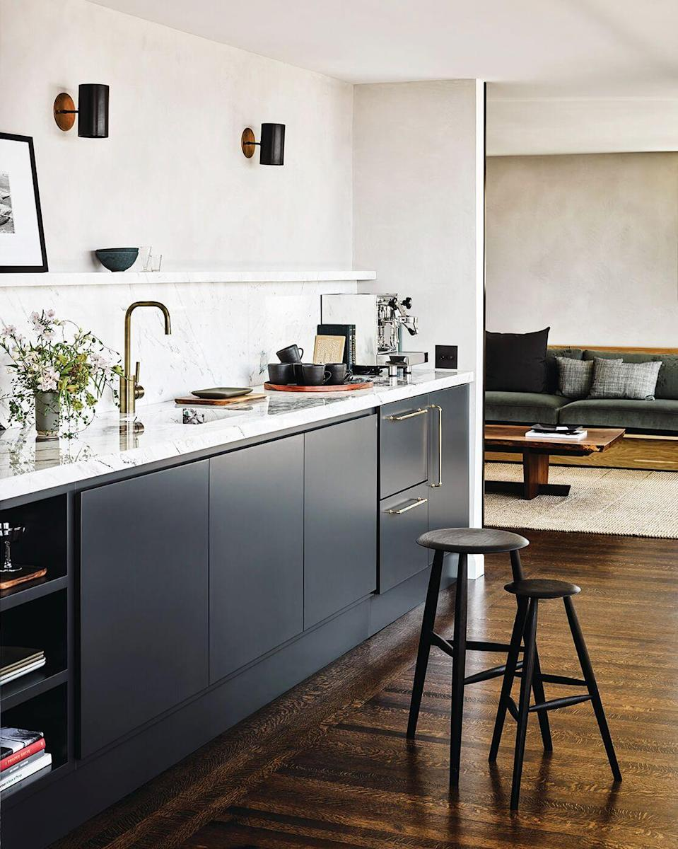 "<p>The narrow shape of the a galley kitchen tends to present some spacial challenges. In this one designed by <a href=""https://www.catherinekwong.com/"" rel=""nofollow noopener"" target=""_blank"" data-ylk=""slk:Catherine Kwong"" class=""link rapid-noclick-resp"">Catherine Kwong</a>, the designer opened things up by ditching upper cabinets in favor of a floating shelf. Opting for sconces instead of a flush mount or pendant helps make the ceilings feel a little higher, too. </p>"