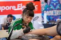 Japanese tattoo artist Noko, 10, working on a client at the Culture Cartel street culture festival on 7 December. (PHOTO: Dhany Osman / Yahoo News Singapore)