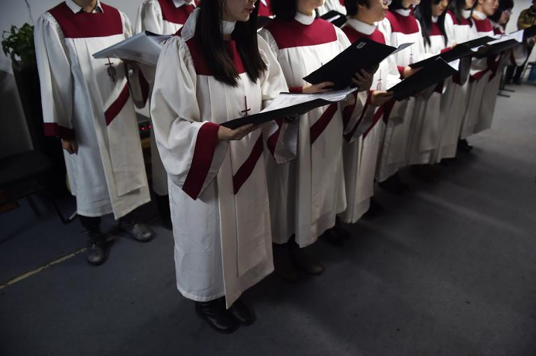 A choir of an underground church sings at a Christmas Eve service at an apartment in Beijing on December 24, 2014