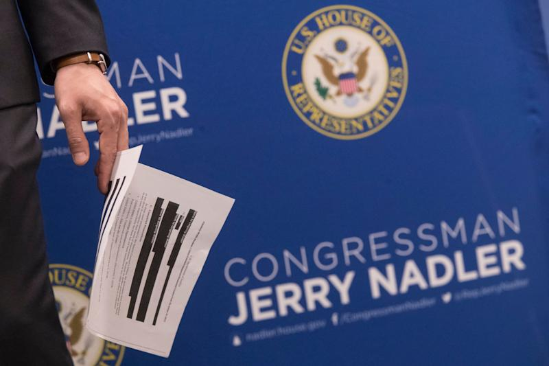 An aide to U.S. Rep. Jerrold Nadler, D-N.Y., chair of the House Judiciary Committee, holds a page from the redacted Robert Mueller report ahead of a news conference, Thursday, April 18, 2019, in New York. (AP Photo/Mary Altaffer)