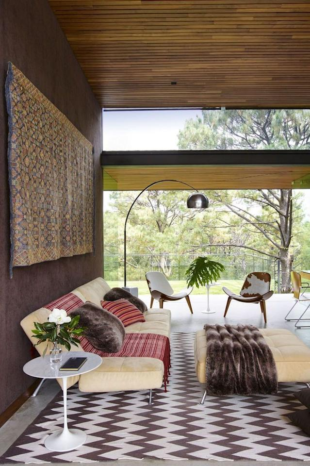 """<p>Brown hues and layers of texture add warmth to a  <a href=""""https://www.elledecor.com/design-decorate/house-interiors/a8879/modern-house-design/"""" target=""""_blank"""">treehouse-style Mexican home</a>. The family room is furnished with a sofa and ottoman by Ligne Roset, along with a Saarinen side table by Knoll, and chairs by Hans Wegner. The Arco lamp is by Flos, the pillows and rug are custom, and the tapestry is made from a traditional Bhutanese man's robe.</p>"""