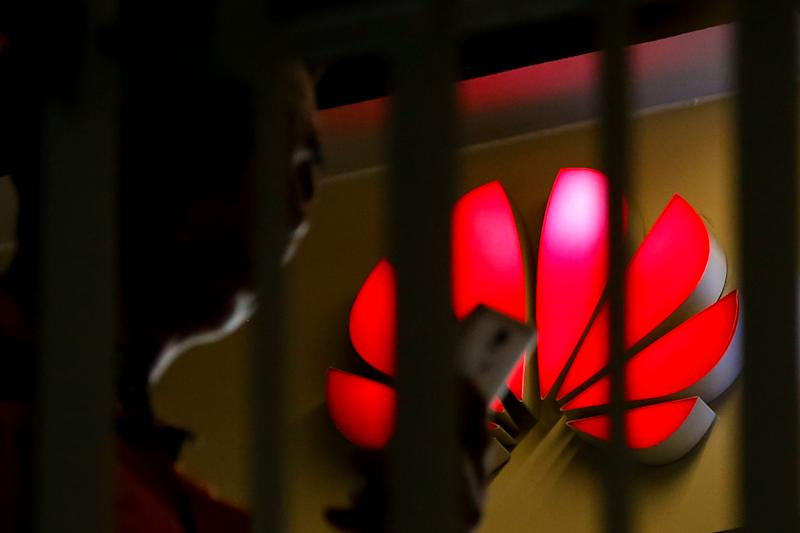 A man looks at his smartphone past a Huawei retail shop is seen through a handrail inside a commercial office building in Beijing, Tuesday, May 21, 2019. (AP Photo/Andy Wong)