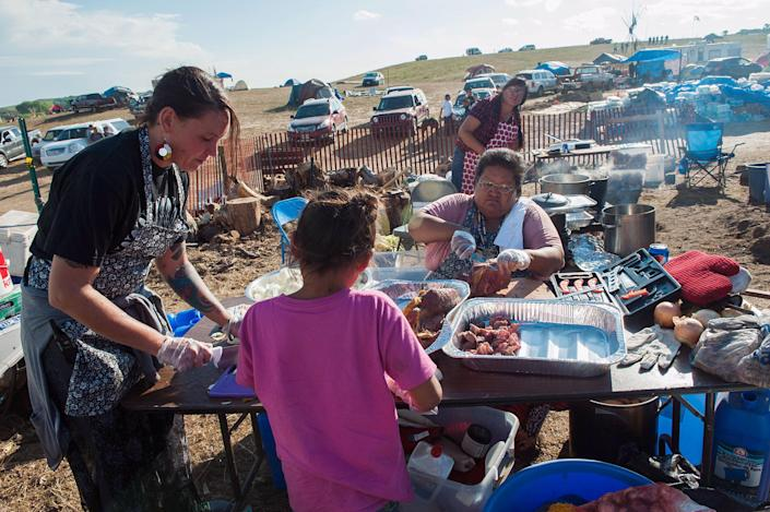 <p>Vandee Khalsa, left, Tatanka Skawin SwiftBird, center, and Winona Kasto prepare buffalo soup for protesters gathered to stop construction of the Dakota Access oil pipeline near the Standing Rock Sioux reservation in Cannon Ball, N.D., on Sept. 6, 2016. (Photo: Andrew Cullen/Reuters) </p>
