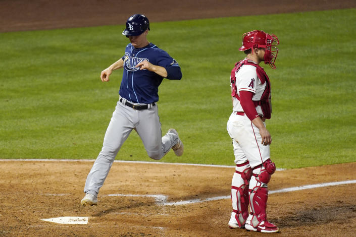 Tampa Bay Rays' Joey Wendle, left, scores on a double by Kevin Kiermaier as Los Angeles Angels catcher Max Stassi stands at the plate during the sixth inning of a baseball game Tuesday, May 4, 2021, in Anaheim, Calif. (AP Photo/Mark J. Terrill)