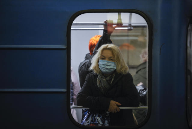 A woman wearing a protective mask as a precaution to the outbreak of Coronavirus rides on a subway in Kiev. (AP/SOPA)