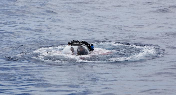 "Seychelles President Danny Faure emerges from the ocean inside a submersible, off the coast of Seychelles on Sunday April 14, 2019. In a striking speech delivered from deep below the ocean's surface, the Seychelles president on Sunday made a global plea for stronger protection of the ""beating blue heart of our planet."" President Danny Faure's call for action, the first-ever live speech from an underwater submersible, came from one of the many island nations threatened by global warming.(AP Photo/Steve Barker)"