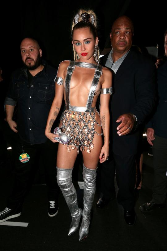 <p>Well, she brought it alright. For her lavender carpet look, Miley Cyrus went for a silver cyborg feel, in an outfit that most definitely came from Hollywood Boulevard. She paired a skirt, which seems to have been made from a chandelier, with silver suspenders that conveniently covered some of her breasts. She accessorized with mini belts on her biceps and matching pointy-toe thigh-high boots. (Photo: Getty Images)</p>