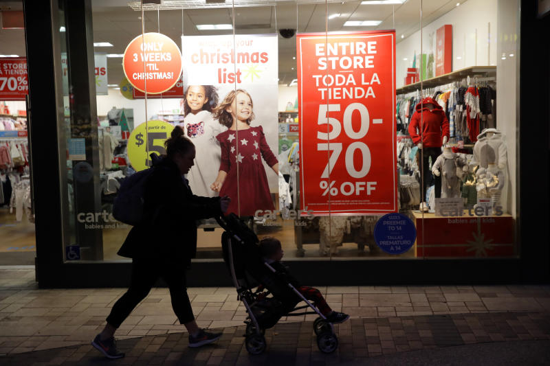 FILE - In this Dec. 16, 2019, file photo a shopper walks in front of sales signs in Santa Clarita, Calif. On Tuesday, Dec. 31, the Conference Board reports on U.S. consumer confidence for December. (AP Photo/Marcio Jose Sanchez, File)