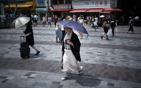 A woman shelters herself from the sun as she walks along a street in Tokyo - Credit: MARTIN BUREAU/AFP/Getty Images