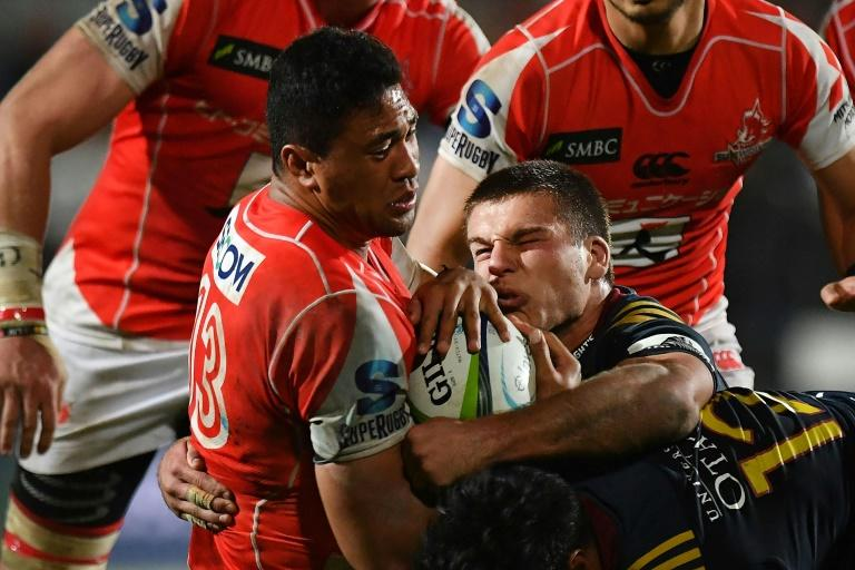 The Sunwolves' William Tupou (L) is tackled by the Highlanders' Dillon Hunt during their Super Rugby match, at Rugby Park in Invercargill, on April 22, 2017