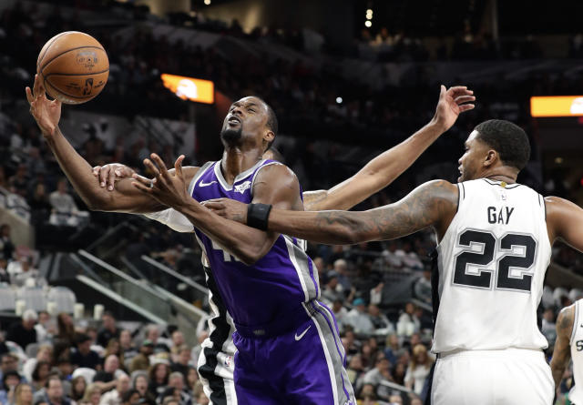 Sacramento Kings forward Harrison Barnes, left, is fouled by San Antonio Spurs forward Rudy Gay (22) as he tries to score during the first half of an NBA basketball game in San Antonio, Friday, Dec. 6, 2019. (AP Photo/Eric Gay)