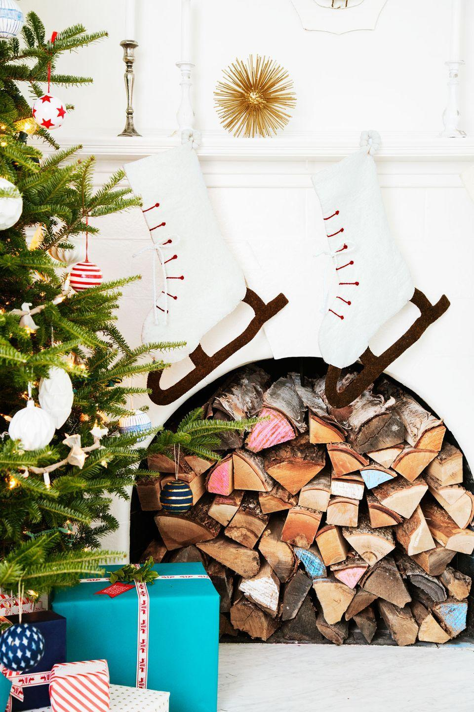 """<p>Filled with split logs (some accented with colorful chalk for extra panache), this non-working fireplace still proves a cozy anchor for this <a href=""""https://www.countryliving.com/home-design/house-tours/g2780/jennaea-gearhart-white-christmas-decor/"""" rel=""""nofollow noopener"""" target=""""_blank"""" data-ylk=""""slk:Tudor house's family room"""" class=""""link rapid-noclick-resp"""">Tudor house's family room</a>.</p><p><a class=""""link rapid-noclick-resp"""" href=""""https://www.amazon.com/Stockings-Holders-Metal-Seasonal-D%C3%A9cor/s?ie=UTF8&page=1&rh=n%3A13744821%2Cp_n_material_browse%3A316589011&tag=syn-yahoo-20&ascsubtag=%5Bartid%7C10050.g.1247%5Bsrc%7Cyahoo-us"""" rel=""""nofollow noopener"""" target=""""_blank"""" data-ylk=""""slk:SHOP STOCKING HOOKS"""">SHOP STOCKING HOOKS</a><br></p>"""